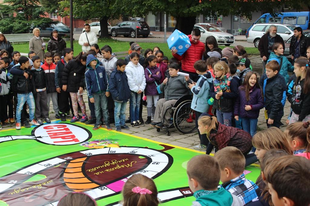 много деца събрани около карта за игра на открито