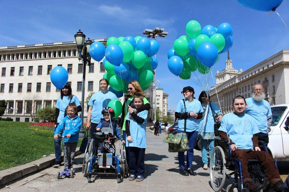 хора на инвалидни колички със сини и зелени балони