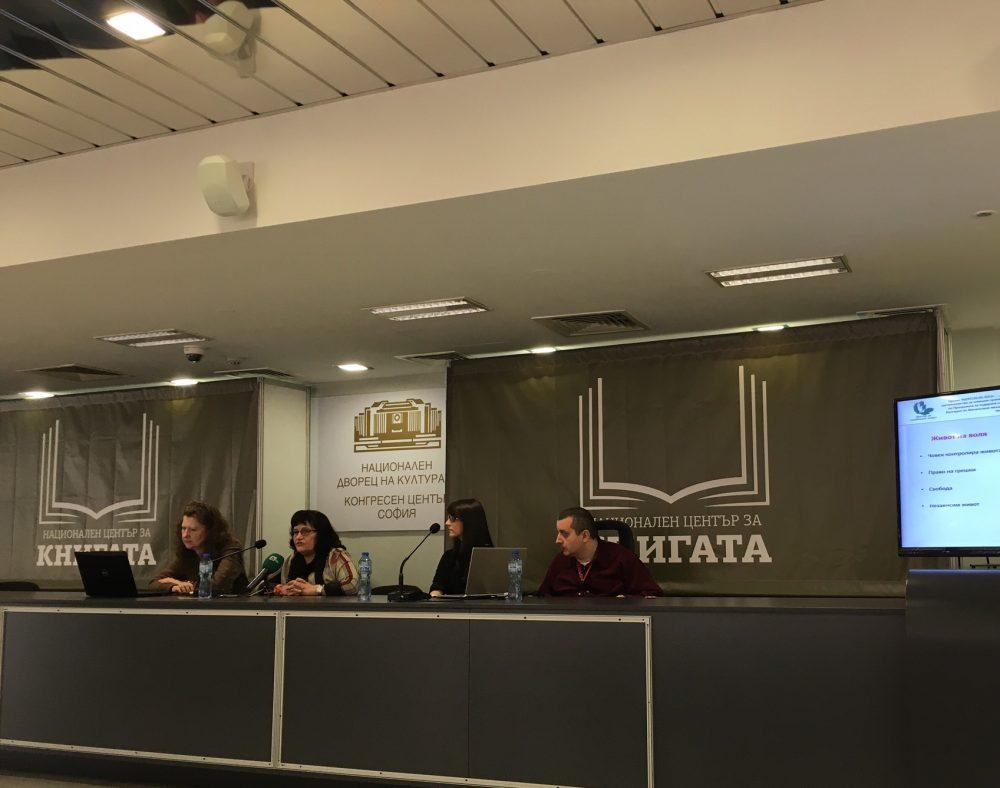 хора седящи на подиум в конферентна зала