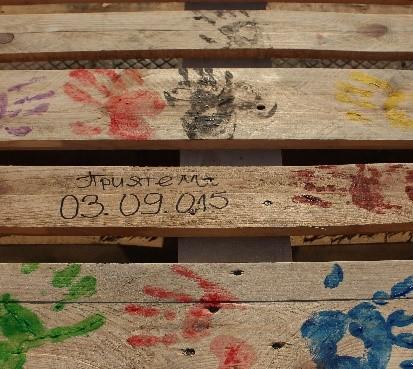 отпечатъци на ръце върху дървена маса с различни бои