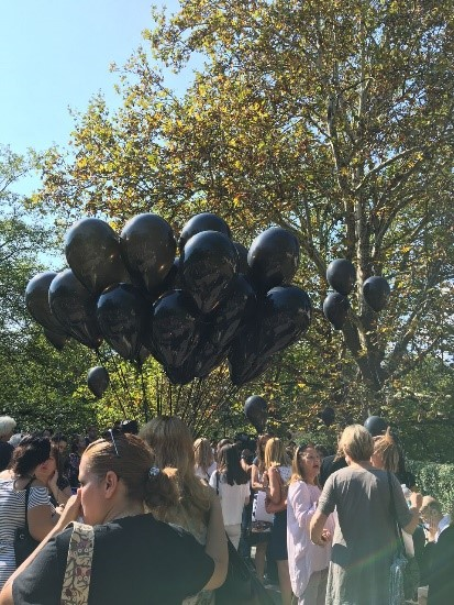 хора с черни балони в ръцете