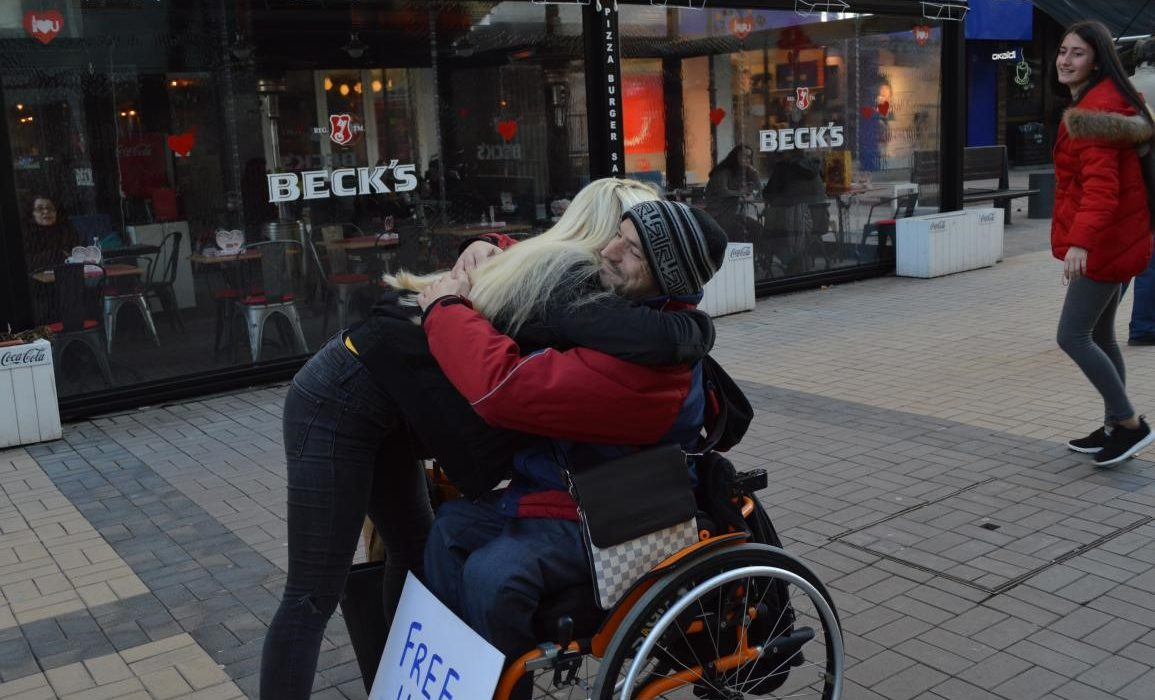 прегръдка между човек в количка и пешеходец