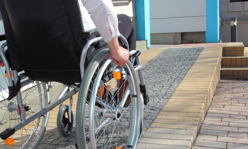 Човек с количка се изкачва по рампа на вход ва блок.